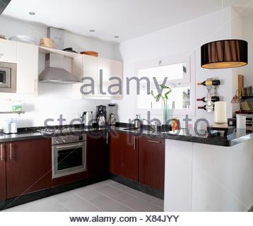 Una moderna cucina bianca con le unità bianche, acciaio inox forno integrale e cappa, pavimento ...