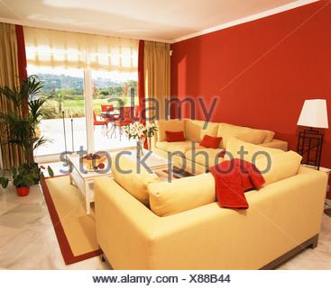 Giallo brillante, divani e parete rossa in un moderno soggiorno con ...