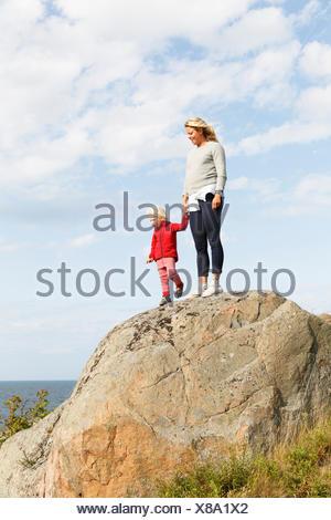 La Svezia, arcipelago di Stoccolma, Sodermanland, Oja, donna in piedi con il figlio (2-3) sulla roccia sotto il cielo con le nuvole Foto Stock
