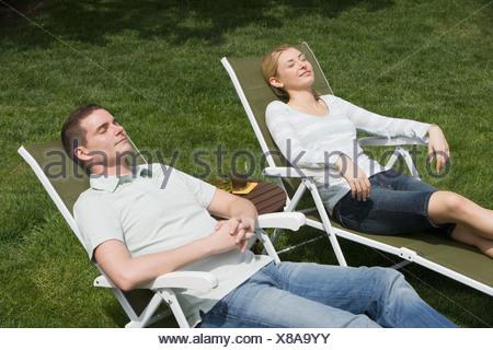Giovane seduto in sedie a sdraio Foto Stock