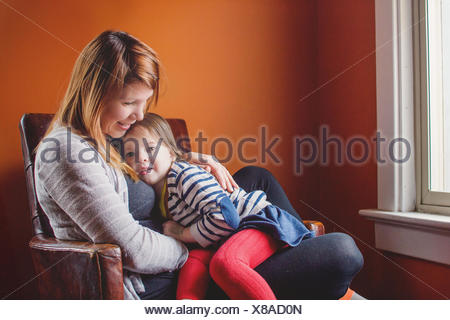 Madre e figlia seduto in una sedia insieme Foto Stock