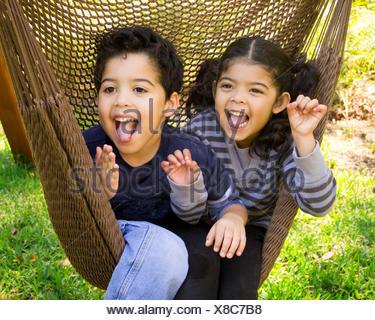 Twin fratello e sorella di seduta in una amaca tirando funny faces Foto Stock