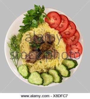Vermicelli con spezzatino di carne e verdure sulla piastra bianca. Isolato su sfondo grigio. Foto Stock