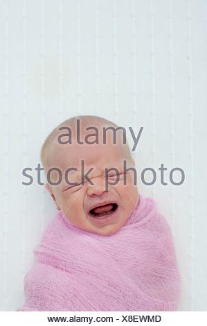 Il bambino piange, avvolto in una coperta Foto Stock