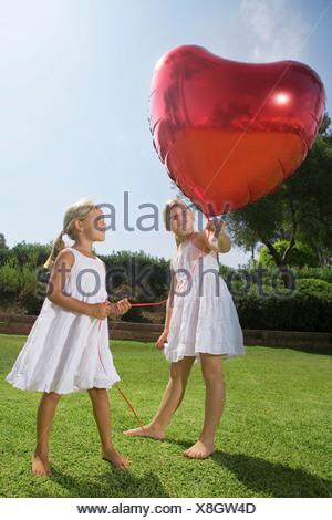 Le giovani ragazze azienda cuore rosso palloncino Foto Stock