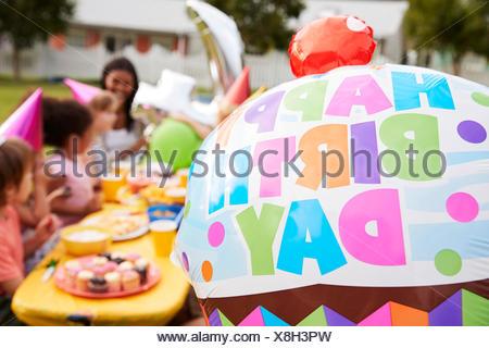 Madre con bambini all'aperto godendo di festa di compleanno insieme Foto Stock