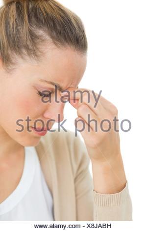 Donna con mal di testa pizzicando il suo naso e wincing Foto Stock