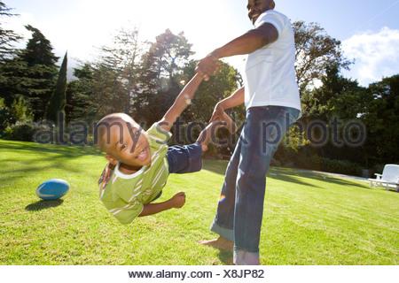 Padre figlio di oscillazione 6-8 anni in aria all'aperto Foto Stock
