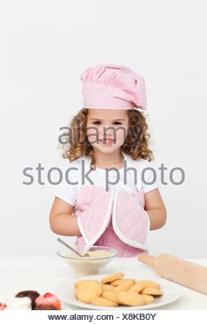 Ragazza carina con guanti da cucina mentre prepara i cookie Foto Stock