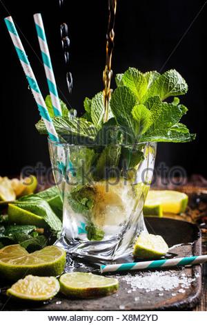 Bicchiere di cocktail mojito con colata di rum e soda, menta fresca, tigli e cubetti di ghiaccio su sfondo nero.