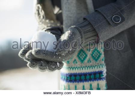 Una giovane donna che tiene una piccola palla di neve nelle sue mani con guanti. Foto Stock