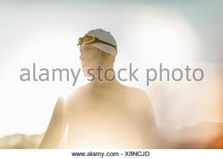 Un nuotatore in una muta umida, nuoto cappello e occhiali di protezione. Foto Stock