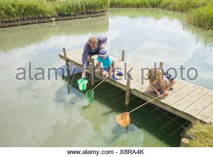 L uomo e i bambini la pesca al largo molo Foto Stock