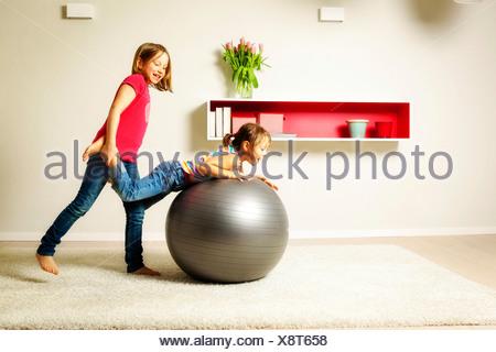 I bambini in soggiorno a giocare con palline rimbalzanti, Monaco di Baviera, Germania Foto Stock