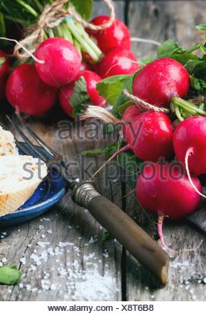 Fresche ravanelli bagnato con forcella vintage, sale marino e pane su un vecchio tavolo in legno Foto Stock