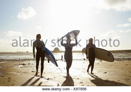 Tre amici di sesso femminile sulla spiaggia, tenendo le tavole da surf Foto Stock