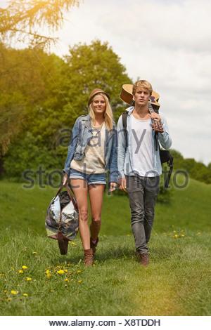 Coppia giovane camminare attraverso il campo con la chitarra Foto Stock