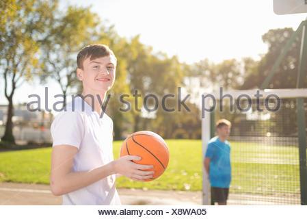 Ritratto di sorridere maschile giovane giocatore di basket sul campo di pallacanestro Foto Stock