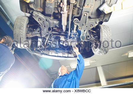 Maschio di studente di college che guarda l'auto in garage officina Foto Stock