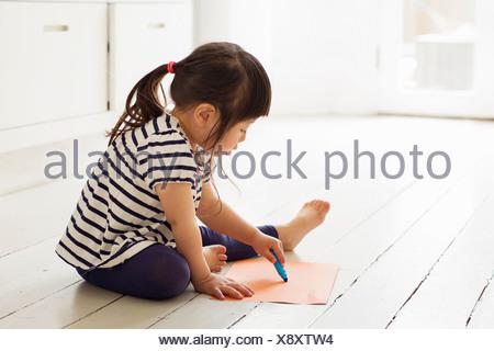Femmina bambino seduto sul pavimento disegno Foto Stock