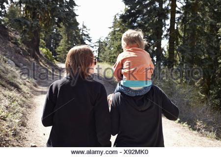 Le donne a camminare attraverso la foresta in Oregon, USA, con il bambino seduto sulle spalle Foto Stock