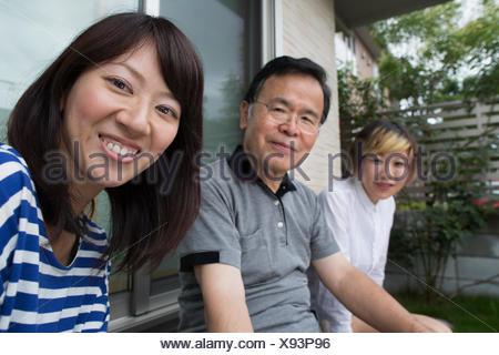 Due donne e un uomo seduto a casa in un giardino. Un padre e due figlie. Foto Stock