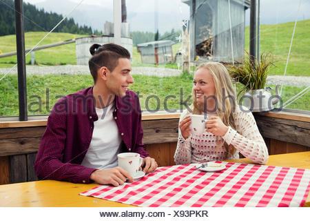 Coppia giovane a bere caffè e parlando in cafe Foto Stock