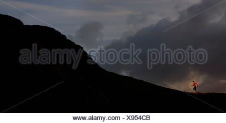 Giovane uomo che corre fino stagliano mountain Foto Stock