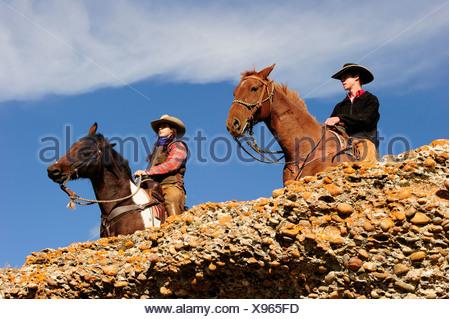 Cowboy e cowgirl su cavalli guardando in lontananza, Saskatchewan, Canada, America del Nord Foto Stock