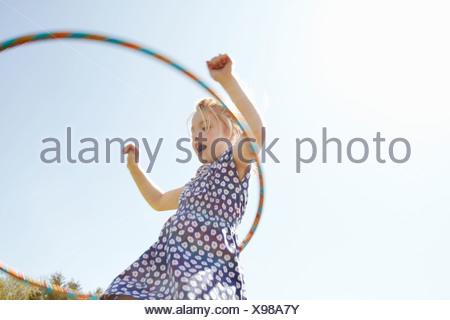 Basso angolo vista della ragazza che gioca con il cerchio in plastica Foto Stock