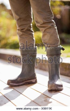 Uomo in stivali in gomma sul pavimento allagato Foto