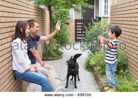 Famiglia con cane, padre sventolare al figlio Foto Stock