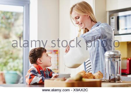 Madre versando il latte in figlio tazza colazione