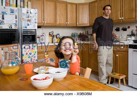 Una giovane ragazza seduta al tavolo di cucina e suo padre in piedi dietro Foto Stock