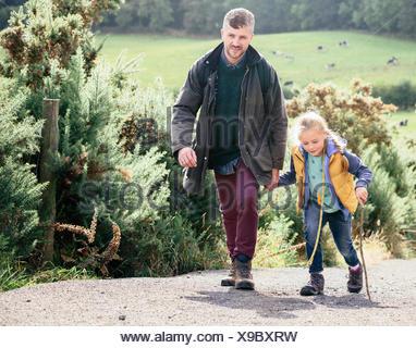 Padre e figlia escursionismo su strada rurale Foto Stock