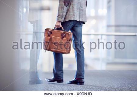 Ritagliato shot del giovane imprenditore con valigetta in conference centre Foto Stock