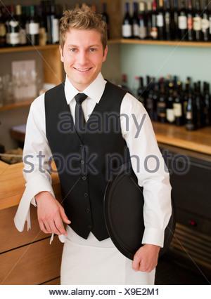 Cameriere appoggiata sul contatore nel ristorante Foto Stock