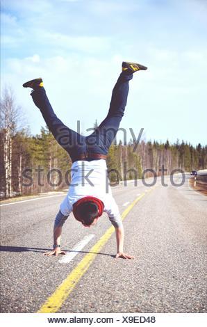 Lunghezza piena vista posteriore dell'uomo facendo Handstand sulla strada di campagna contro il cielo nuvoloso Foto Stock