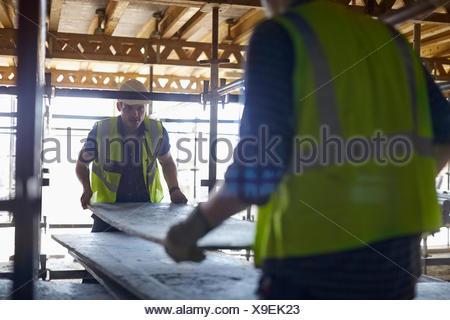 Lavoratori edili plyboard di sollevamento al sito in costruzione Foto Stock