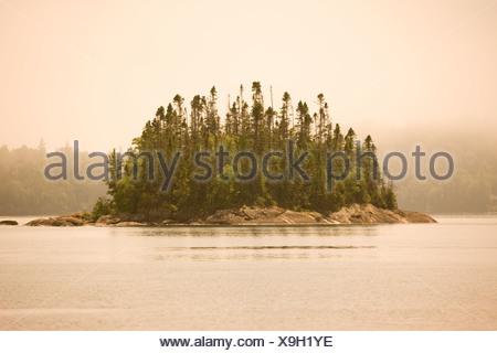 Isola di nebbia nella baia di ordito come si vede da una canoa/kayak o escursione in campeggio lungo il lago superiore il sentiero costiero Lago Superiore provinc Foto Stock