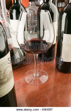 Vino rosso vetro e bottiglie Foto Stock