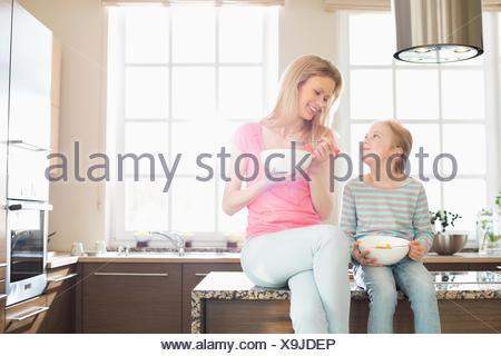 Felice madre e figlia di fare colazione in cucina