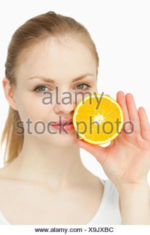 Donna collocando un arancio sulle labbra Foto Stock