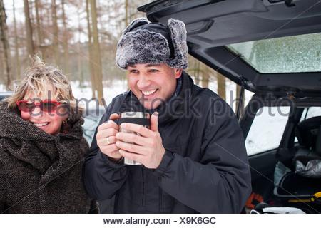 Madre e figlio avente una bevanda calda al di fuori in inverno Foto Stock