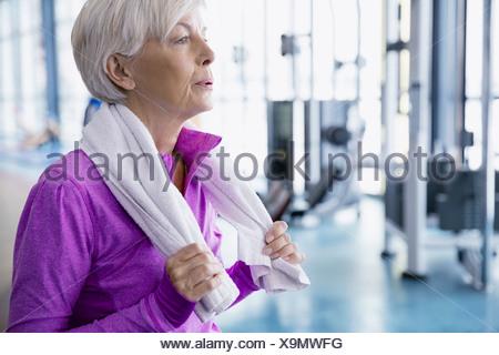 Donna con asciugamano in appoggio alla palestra Foto Stock