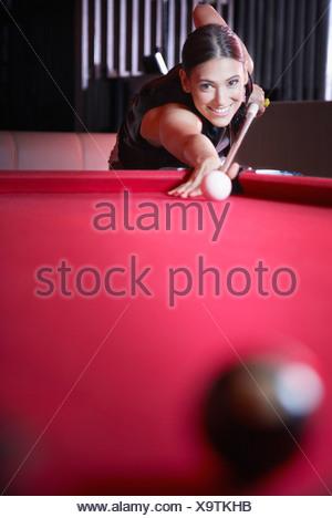 Donna giocando a biliardo e sorridente Foto Stock