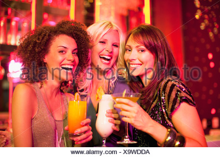 Gli amici a bere un cocktail in discoteca Foto Stock