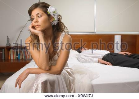 Annoiato sposa con lo sposo addormentato in background Foto Stock
