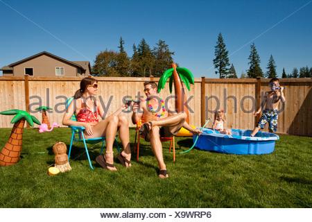Famiglia nel cortile con la piscina per bambini e cocktail