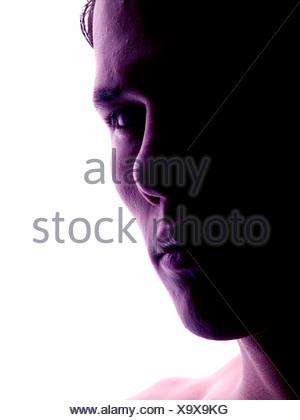 La faccia di un giovane serio in controluce Foto Stock